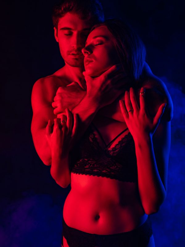 passionate undressed sexy young couple hugging in red light